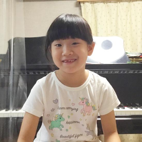 ピアノの前に座って微笑む生徒さんの写真