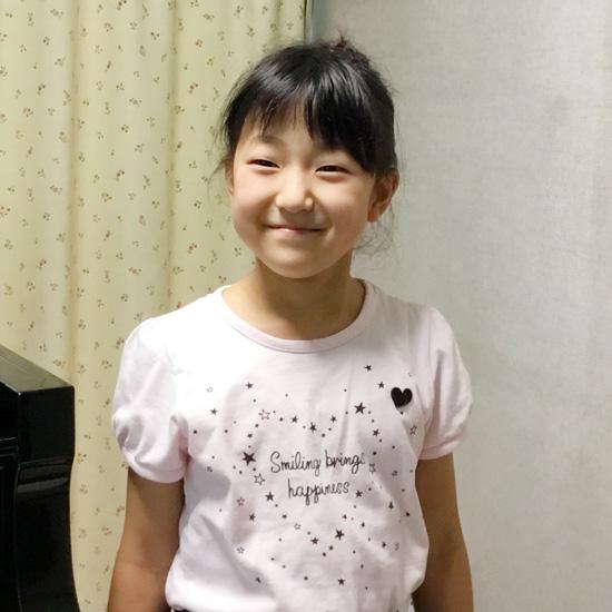 レッスン室で微笑む女の子のピアノ生徒さんの写真